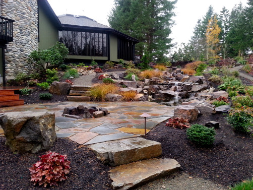 Fire pit and patio to gather by the water feature